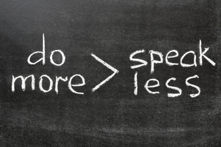 interpretation of famous phrase speak less do more handwritten on blackboard Stock Photo