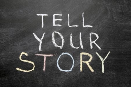 phrase: tell your story phrase handwritten on the school blackboard