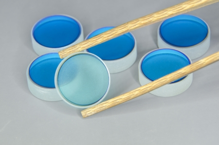 closeup of optical mirrors batch with focus on selected one by wooden tweezers photo