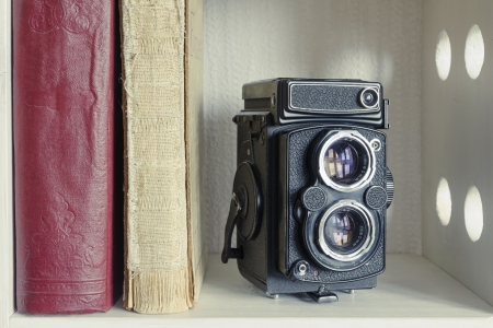 vintage TLR photo camera with old books on  the white shelf photo