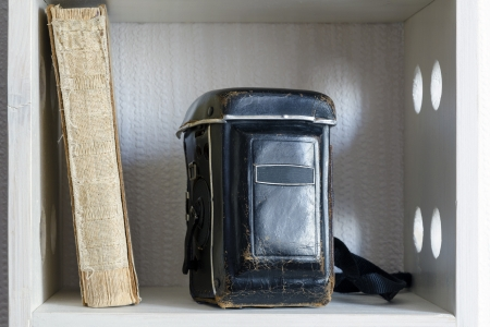 leather case of TLR photo camera with old ragged book on the shelf photo