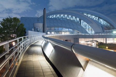 dome building: pedestrian pathway with metallic handrail leads toward modern arc dome building by night Stock Photo