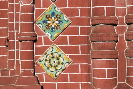 detailed red brick wall fragment of ancient Russian Orthodox Church in Yaroslavl city with traditional ceramic tile decoration photo
