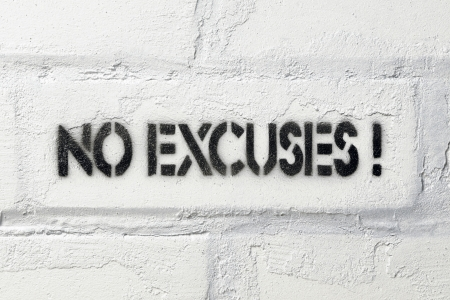 no excuses exclamation stencil print on the white brick wall Stockfoto