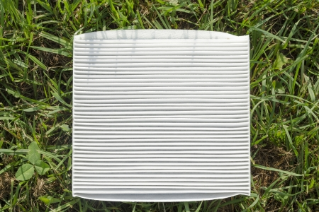 clean white air filter on the green grass Фото со стока