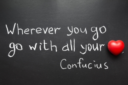 famous Confucius quote  Wherever you go, go with all your heart  handwritten on blackboard Stok Fotoğraf