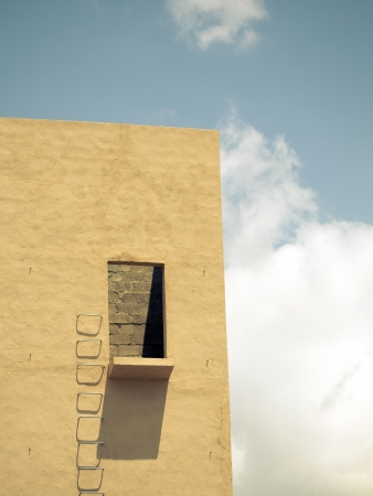 metallic stairs: building wall with metallic stairs and cloudy sky Stock Photo