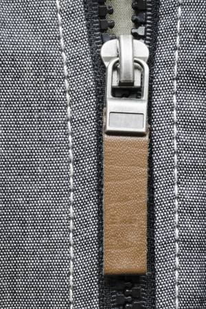 fragment of open plastic zipper fastener with brown leather tag photo