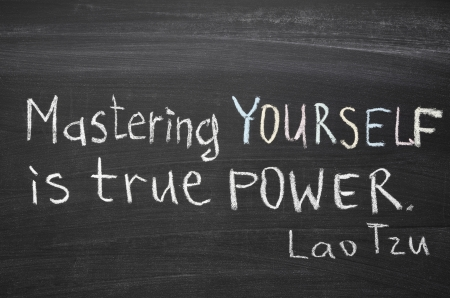 excerpt from famous Lao Tzu quote  Mastering others is strength  Mastering yourself is true power   handwritten on blackboard