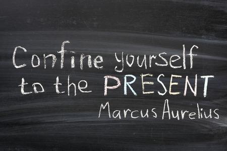 confine: famous Marcus Aurelius quote  Confine yourself to PRESENT  handwritten on blackboard Stock Photo