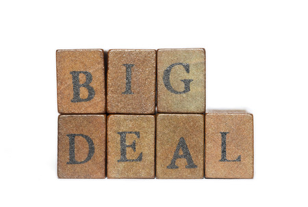 big deal: big deal phrase made from wooden bricks isolated on white