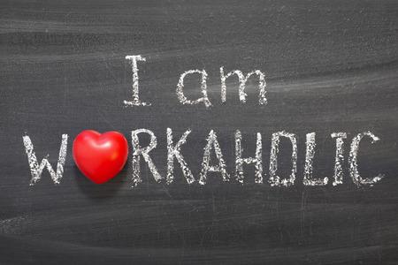 I am workaholic phrase handwritten on blackboard with red heart symbol photo