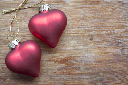jointed: two toy hearts jointed by knot on vintage wooden table