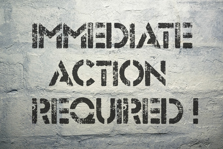 immediate: immediate action required exclamation stencil print on the grunge white brick wall Stock Photo