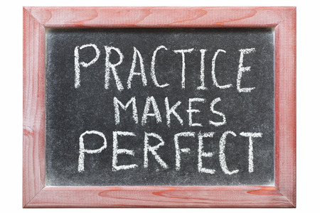practice makes perfect phrase handwritten on vintage blackboard photo