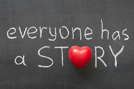 everyone has a story phrase handwritten on chalkboard with heart symbol instead of O