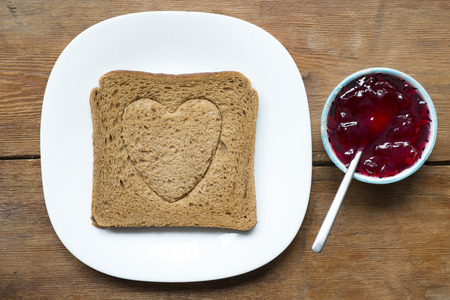 embossing: grilled toast with heart embossing and plate with jam Stock Photo