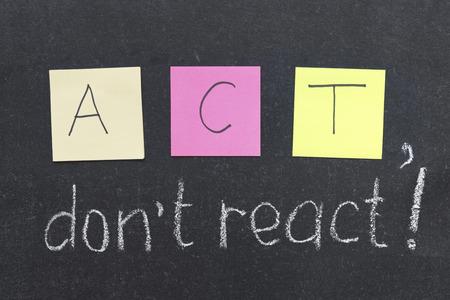 react: ACT, do not react phrase handwritten on blackboard