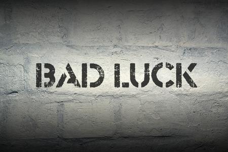 mala suerte: impresi�n de la plantilla de mala suerte en la pared de ladrillo del grunge con efecto de degradado