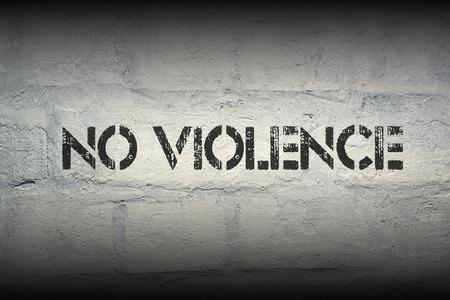 no violence stencil print on the grunge white brick wall Фото со стока
