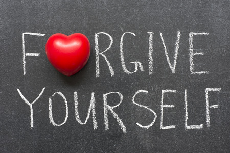 forgive yourself phrase handwritten on school blackboard Stock Photo