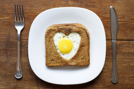 fried toast with egg served on white plate
