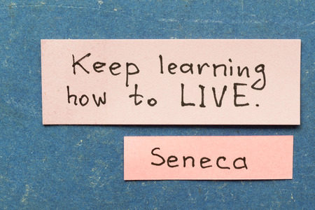interpretation: famous ancient Roman philosopher Seneca quote interpretation with sticky notes on vintage carton board about keep learning