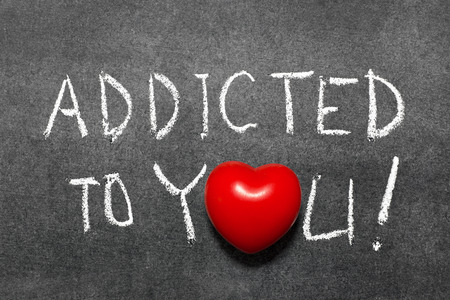 adoration: addicted to you phrase handwritten on blackboard with heart symbol instead of O