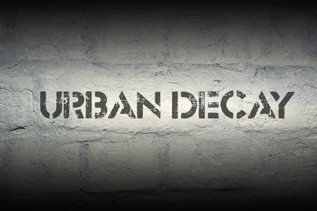 urban decline: urban decay stencil print on the grunge white brick wall Stock Photo