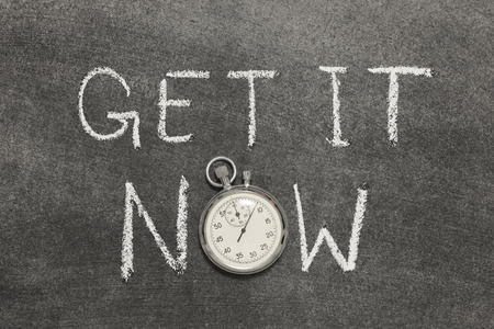 precise: get it now phrase handwritten on chalkboard with vintage precise stopwatch used instead of O