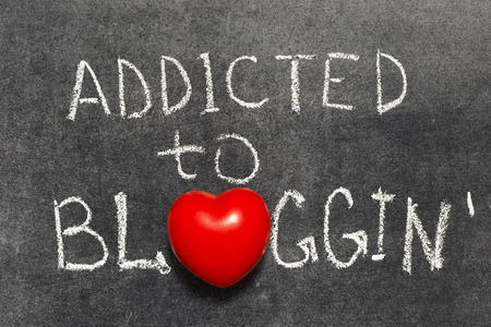 addicted to blogging phrase handwritten on blackboard with heart symbol instead of O Stok Fotoğraf