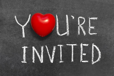invited: you are invited phrase handwritten on blackboard with heart symbol instead of O