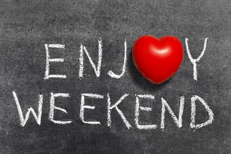 enjoy weekend phrase handwritten on blackboard with heart symbol instead of O Фото со стока - 32380975