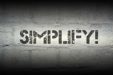 vereenvoudigen: vereenvoudigen stencil print op de grunge witte bakstenen muur Stockfoto