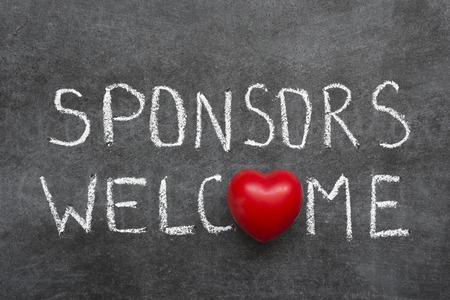 acogida: patrocinadores frase de bienvenida escrita a mano en la pizarra con el s�mbolo del coraz�n en lugar de O Foto de archivo