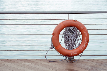 handrails: red lifebuoy hanged on metallic handrails with blue water behind Stock Photo