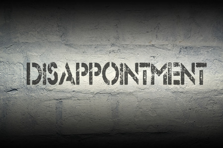 disappointment: disappointment stencil print on the grunge white brick wall