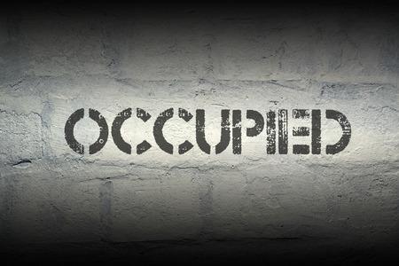 occupied stencil print on the grunge white brick wall