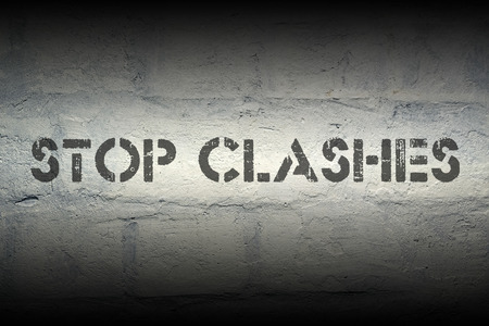 clashes: stop clashes stencil print on the grunge white brick wall Stock Photo