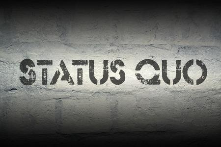 quo: status quo stencil print on the grunge white brick wall