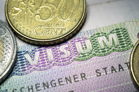 schengen: fragment of European Union Schengen Visa stamp in passport and few Euro coins Stock Photo