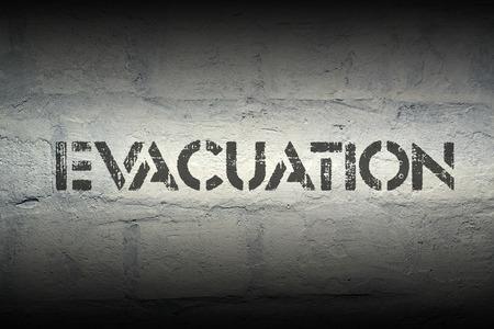 evacuacion: impresi�n de la plantilla de evacuaci�n en la pared de ladrillo blanco de grunge Foto de archivo