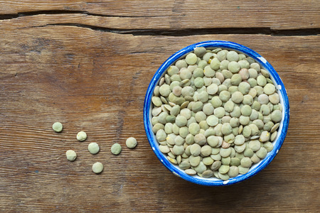 green lentil: dry green lentil beans in small blue cup on vintage wooden table
