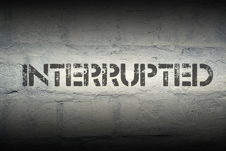 interrupted: interrupted stencil print on the grunge white brick wall Stock Photo