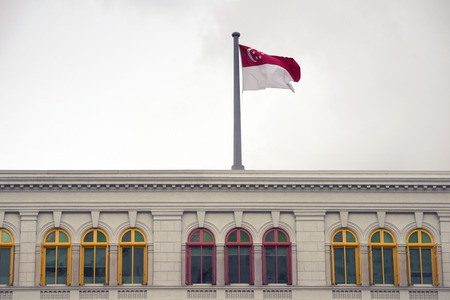police state: state Singapore flag on the top of old police station building