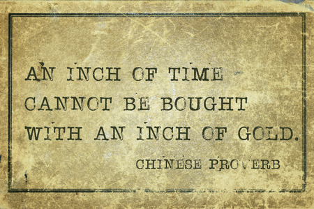 proverb: An inch of time cannot be bought - ancient Chinese proverb printed on grunge vintage cardboard Stock Photo