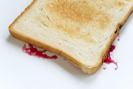 sandwich fallen upside down with jam splashes on white