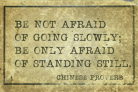 proverb: Be not afraid of going slowly - ancient Chinese proverb printed on grunge vintage cardboard