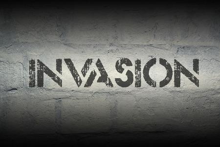 incursion: invasion pochoir impression sur le mur de briques blanches grunge