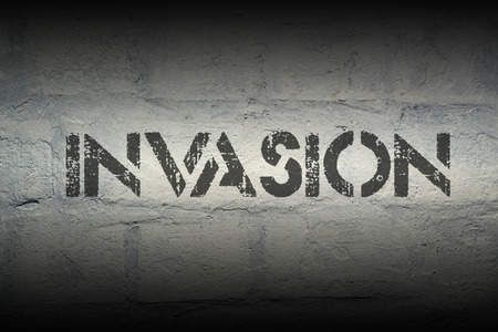 incursion: invasion stencil print on the grunge white brick wall Stock Photo